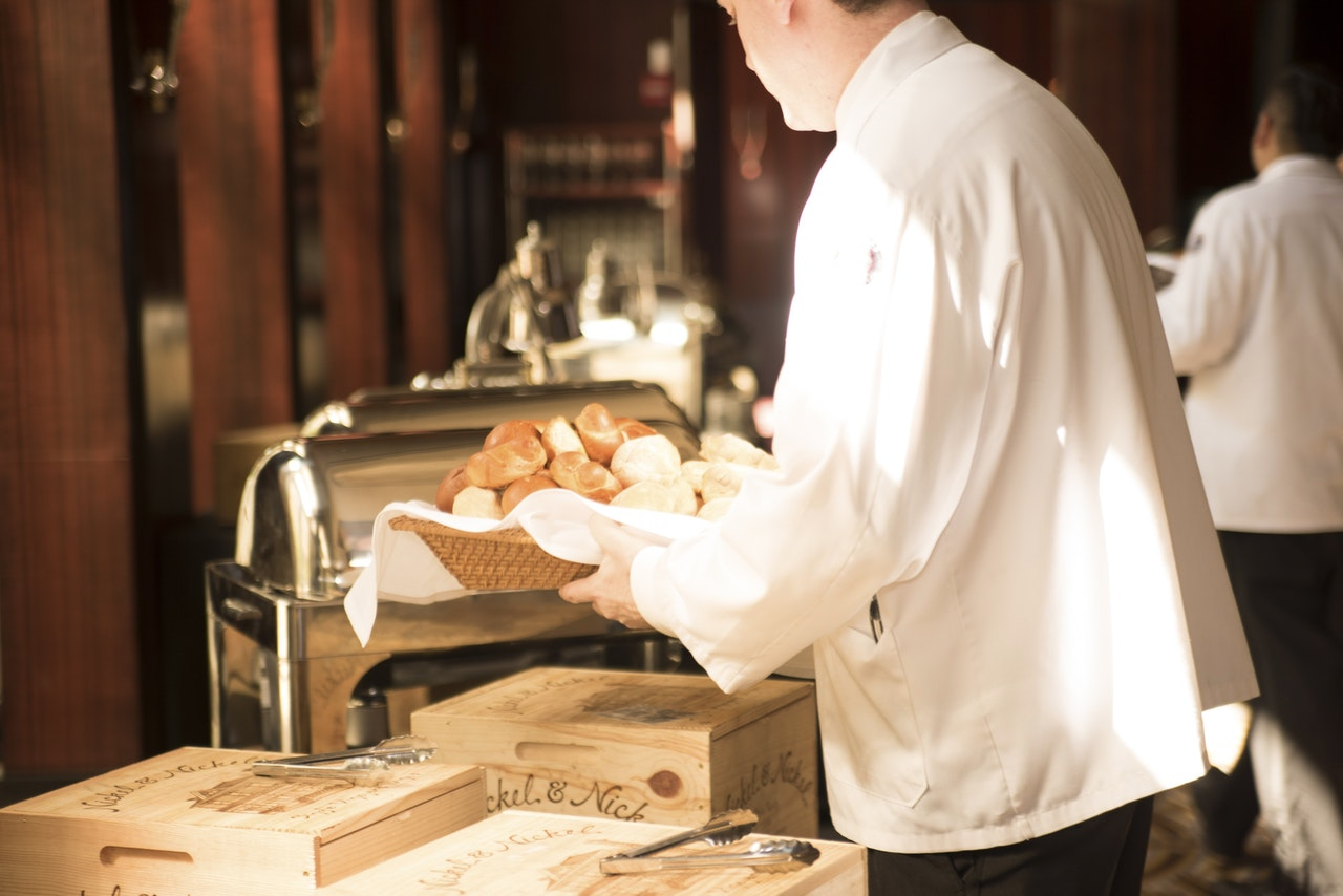 elegant waiter holds bake goods breakfast